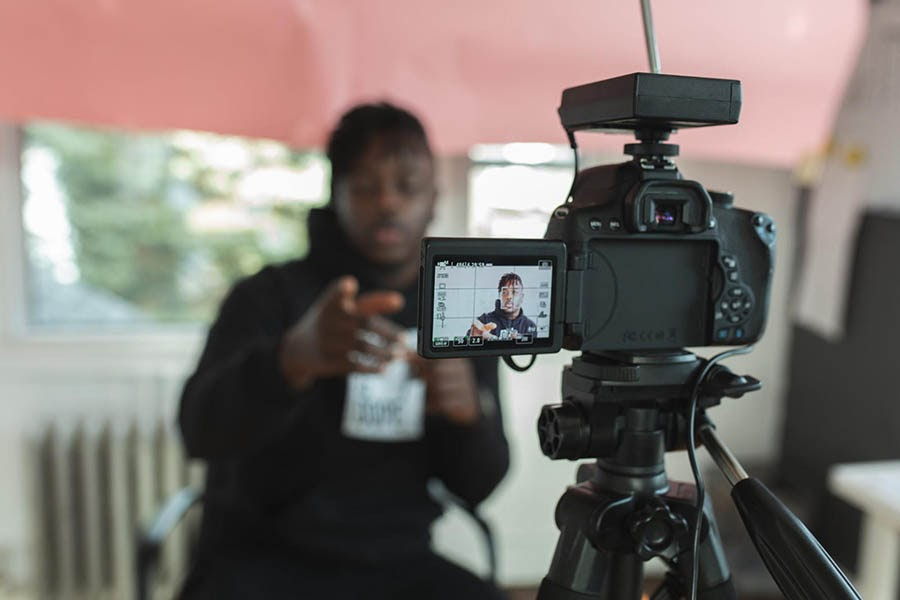 Young man recording himself on a video camera.